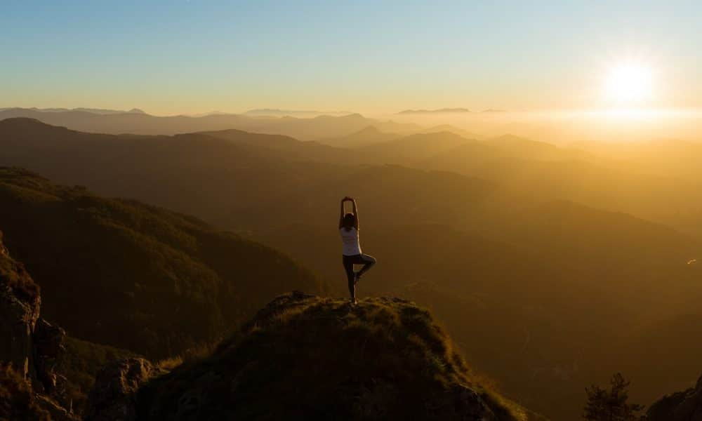 Woman Doing Yoga on Mountain